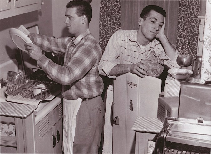"""Home Team: In November of 1957, a pair of 25-year-old Rangers pose, according to the original caption, in their New York bachelor apartment.  """"From the rink to the sink where Marcel Paille (left) is whipping a bowl of something or other and teammate Camille Henry seems to be in one of those trances common to people trying to think up a menu."""""""