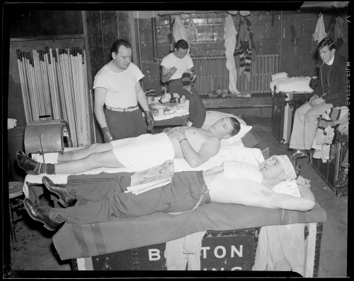 The Worn, The Torn: Boston trainer Win Green (in the rubber gloves) tends to a couple of Bruins, circa 1939. That's Dit Clapper in the towel and stripy socks with his ankle in the ... toaster? Reading the funnies in the foreground, resting his wounded head: Bill Cowley, possibly? (Courtesy of the Boston Public Library, Leslie Jones Collection)