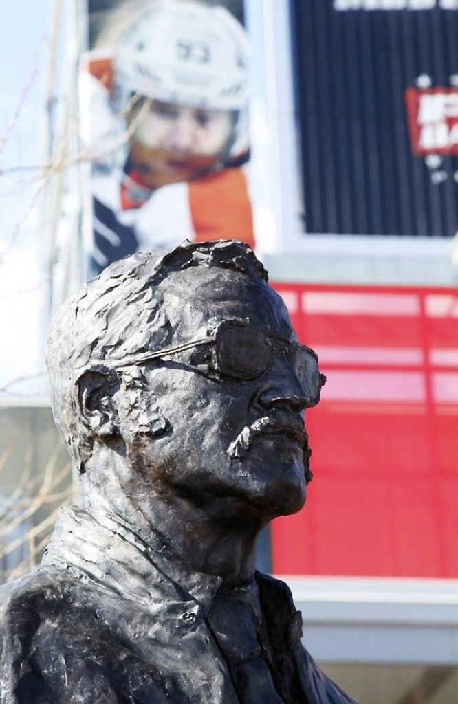 "Coach Fog: Four months after Fred Shero was inducted into the Hockey Hall of Fame in Toronto, the Flyers unveiled a statue of their championship coach on March 15. Sculptor Chad Fisher's 8-foot, 1,300-pound bronze work stands on the site of the old Spectrum. Bernie Parent, for one, was pleased. ""This statue,"" he said, ""will be standing in the heart of Philadelphia as a reminder to all fans back then, all fans now, and all fans to come, that Fred Shero was truly the best coach one of the best human beings this city has and ever will see."" (Photo: Chad Fisher)"