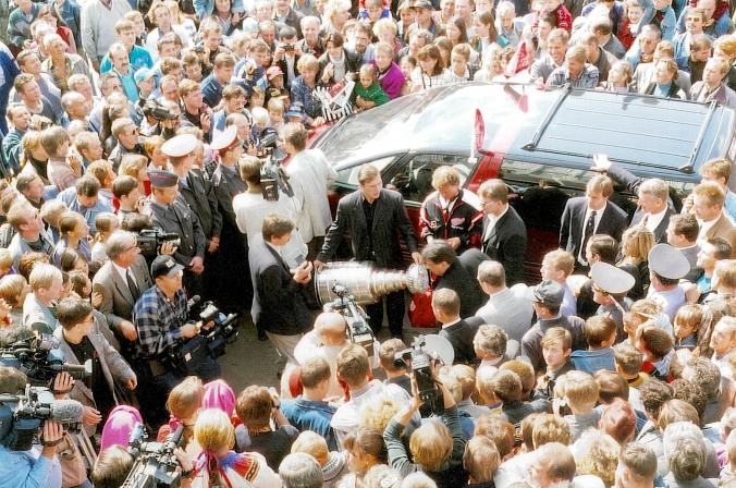 Homecupping: Viacheslav Kozlov of the Detroit Red Wings brings the Stanley Cup to his hometown of Voskresensk, southeast of Moscow, on August 19, 1997. Red Wings owner Mike Illitch is Kozlov's left, with Cupkeeper Phil Pritchard from the Hockey Hall of Fame two over from him. (Photo: Stephen Smith)