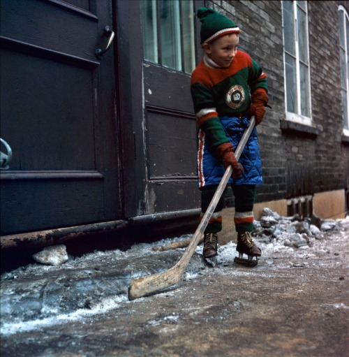 Ace de Québec: Boy with stick and skates on the street of the provincial capital, circa the latter 1950s. (Photo: Rosemary Gilliat Eaton, Bibliothèque et Archives Canada)