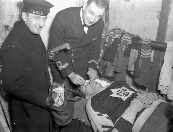 Battledressing: Sub-Lieutenant J.C.Fritz, defenceman with the Royal Canadian Navy's hockey team, takes treatment for a wound suffered during a game in Halifax, Nova Scotia, on February 18, 1943. (Credit: John Merriman / Dept. of National Defence / Library and Archives Canada / PA-107134)