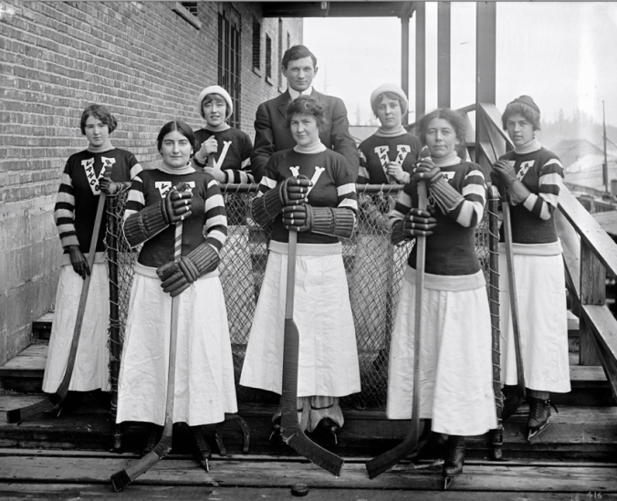 The Vancouver Ladies' Hockey Team line up on the steps of the Denman Street Arena circa 1914. Back row, left to right, they are Connie Smith (right wing), Betty Hinds (rover), Pete Muldoon (manager), Nellie Haddon (centre), Miss Matheson (left wing). From, from left: Mrs. French (coverpoint), Mrs. L.N. McKechnie (goal), Mrs. Percival (point). (Photo: Stuart Thomson, City of Vancouver Archives)