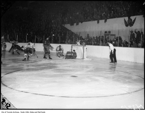 Game Over: A few fans have begun to celebrate. On the ice we see, from the right, referee Bill Chadwick. Behind the net, Habs' defenceman Tom Johnson (10) tussles at Howie Meeker. Gerry McNeil sits while Bill Barilko arises. Butch Bouchard stands in front, looking lost, while Leaf Harry Watson (4) makes for the goalscorer. In the far corner, Cal Gardner (17) lifts his stick while Maurice Richard mimics Barilko's heroic moment. Hard to say who the fifth Hab is, far left.