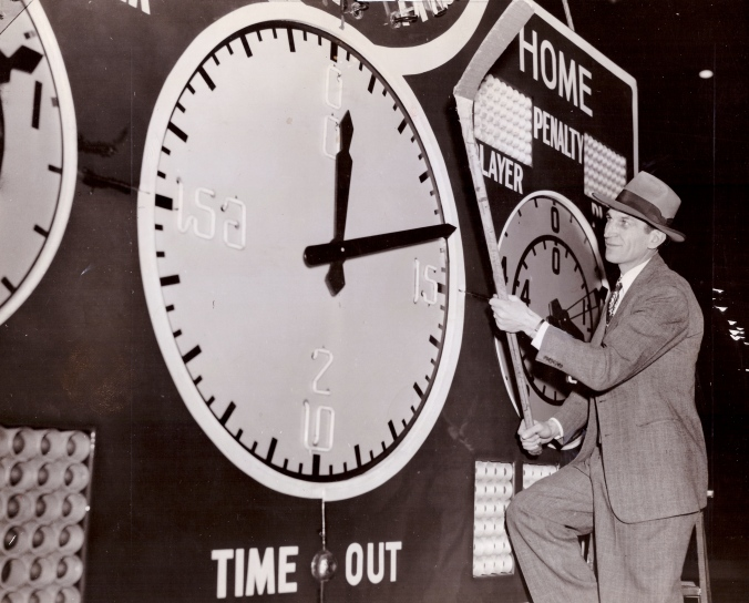 Hometime: Black Hawk left winger Johnny Gottselig poses with Chicago's new centre-ice Bulova clock before it's raised to the Stadium rafters in 1943.