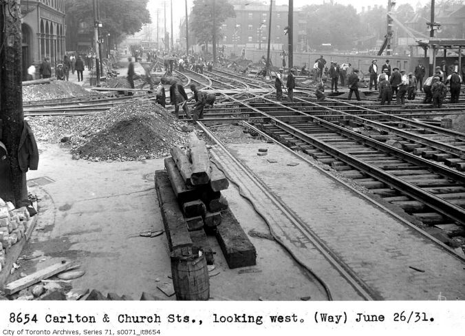Leafs Rebuild: A Toronto Transit Commission photograph showing work on streetcar tracks in late June of 1931 with the MLG construction site in the background.