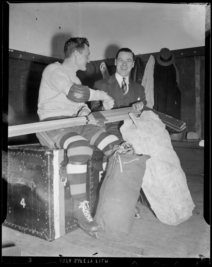 Gladhanders: Bruins' centre Cooney Weiland makes merry with goaltender Tiny Thompson (and sticks) in Boston Garden circa the mid-1930s. (Photo: Courtesy of the Boston Public Library, Leslie Jones Collection)