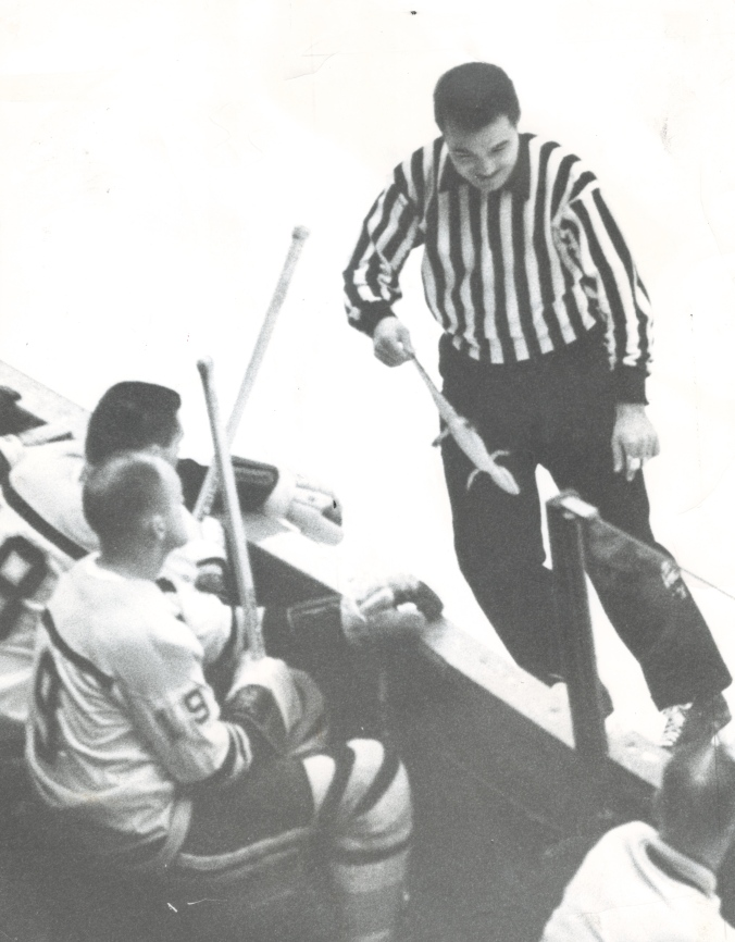 "In The Reptile House: Referee Matt Pavelich dispenses with what some papers called ""a lizard"" in their reports while Bruins Doug Mohns (19) and (next to him) Ed Westfall sit by. ""At first everyone thought the lizard was alive,"" one captioner wrote, ""but it proved just as phoney as the Bruins."" (AP)"